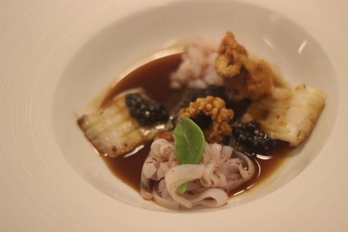 Calamares salteados, confitado, con royal de cebolla, su tinta y caldo caliente de pasamar y calamar con toques de jengibre